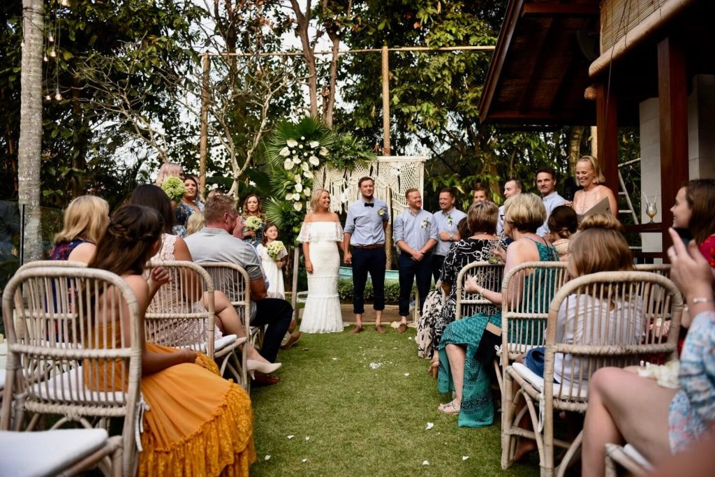 This is a picture of the ceremony. The couple are standing before a stunning macrame arbour.